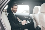 business man in backseat of car with laptop