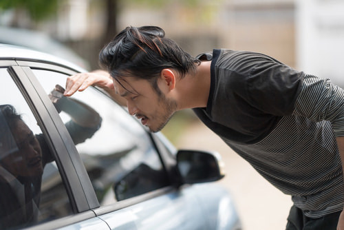 man looking into the passenger compartment of a parked vehicle