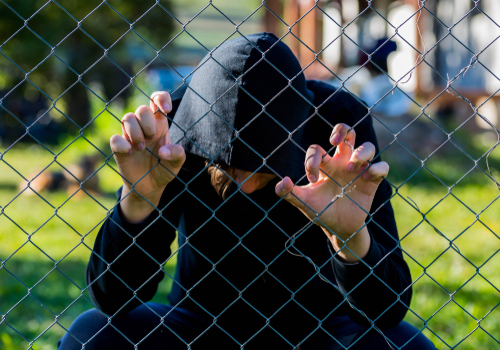 boy in hoodie behind chain-link fence