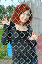 girl behind jail fence