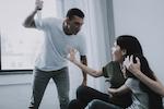 man hitting woman and child