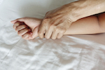 male hand holding down woman's hand in bed