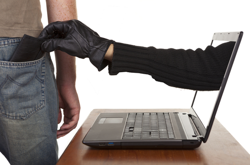 thief's hand reaching out of computer into person's pocket