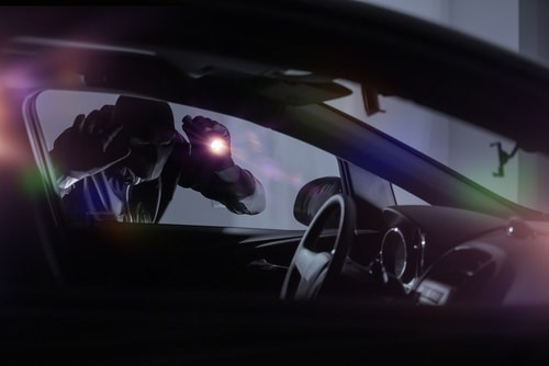 car burglar casing a car as an example of grand theft auto