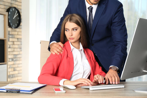 Female employee getting touched unwantingly, as an example of workplace harassment.