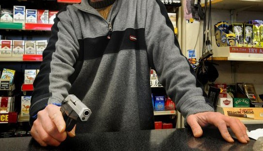 Man-holding-pistol-behind-store-counter