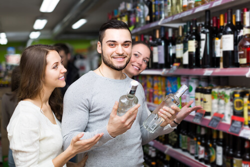 group of people selecting bottles of alcohol from a store shelf