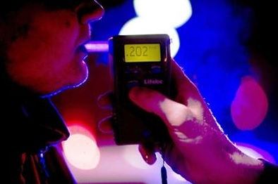 man blowing a .202 into a handheld breath testing device at night