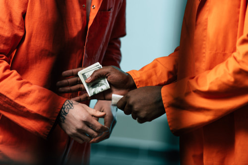 jail inmate handing cash to a fellow inmate