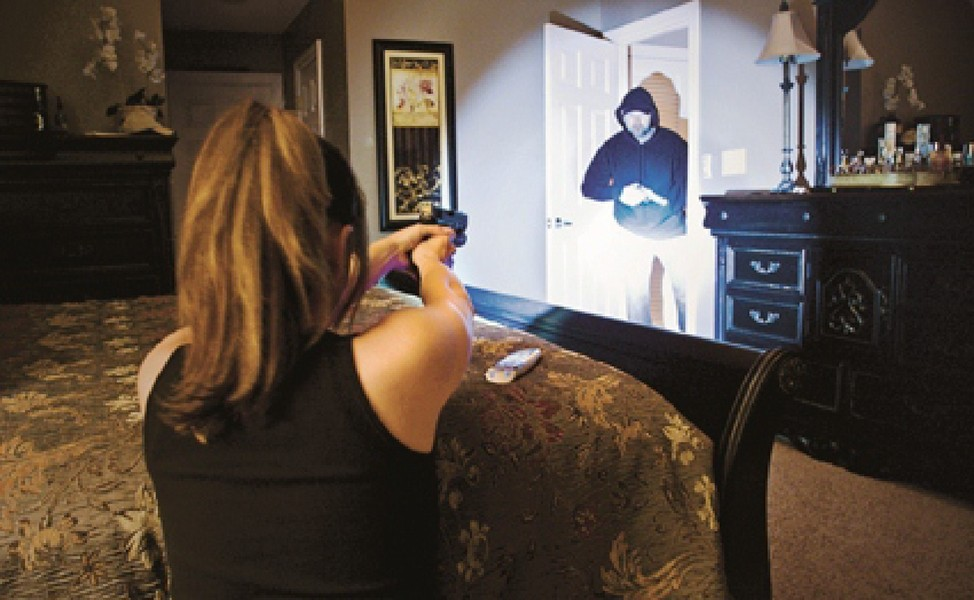 Woman holding a gun to a burglar.