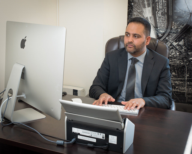 Shouse Law Group attorney Karthik Krishnan at a desk behind a computer