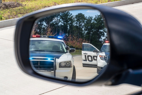 Side mirror view of police following the car. If the driver disobeys an order to stop, the driver could be charged with evading.