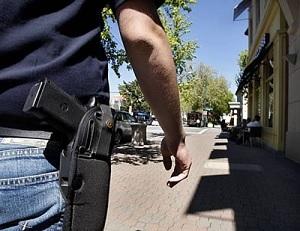 Man-walking-down-street-with-gun-in-holster