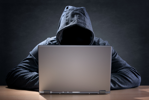 hooded man browsing on a laptop as an example of a Penal Code 311 PC violation
