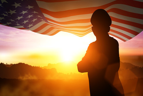 veteran soldier standing in the sun next to flag