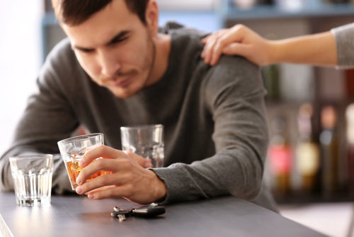 man holding an alcoholic drink while looking down