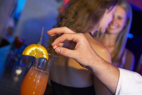 man putting drug in drink at club