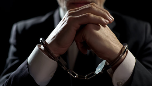 suited man in handcuffs - a violation of 484g PC can lead to up to 3 years in jail