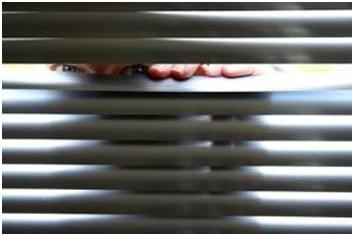 Man peeping through horizontal blinds