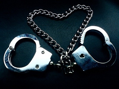 hand cuffs with the chain forming a heart sign