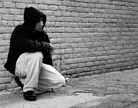 young person kneeling against brick wall