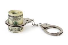 Wad of cash in handcuffs, signifying inmates' cash accounts in jail.
