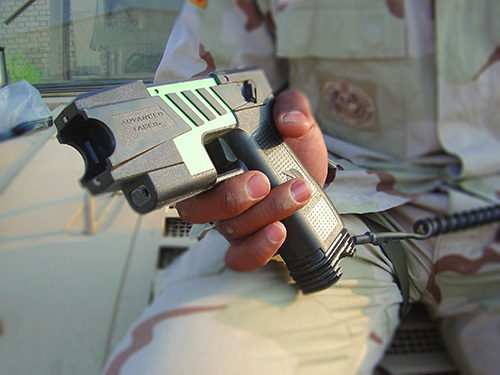 military man holding stun gun; these weapons are generally legal to have in California