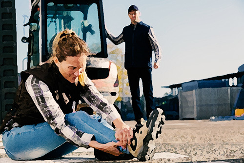 woman tending to a sprained ankle in front of a forklift as an example of an injury covered under workers' compensation in California