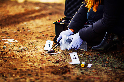 crime scene investigator collecting shell casings; firing rounds into the air can be an example of criminal negligence