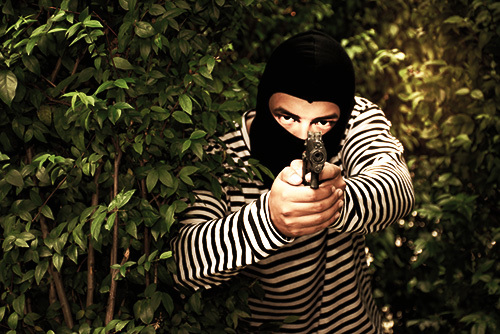 masked man in bushed pointing a pistol as an example of lying in wait murder