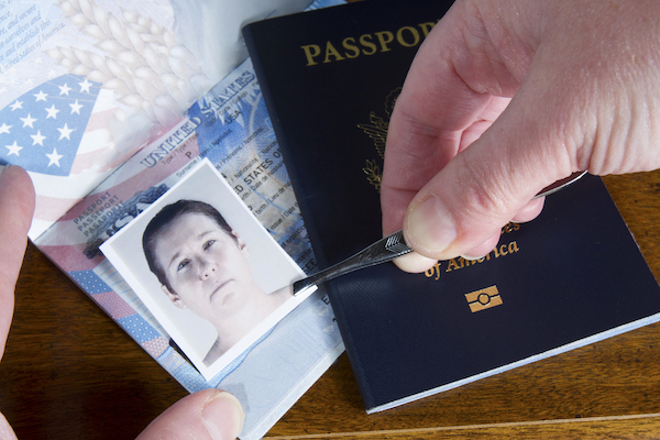 Close-up of hands forging a passport by pasting on the wrong photo.