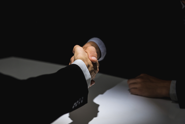 Two people shaking hands in the shadows after conspiring to break the law.