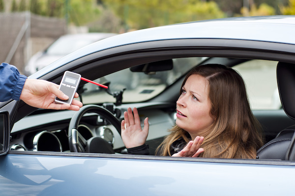 A woman about to take a preliminary breath test after being pulled over for her second DUI.