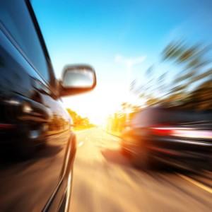 cars speeding around motorcycles