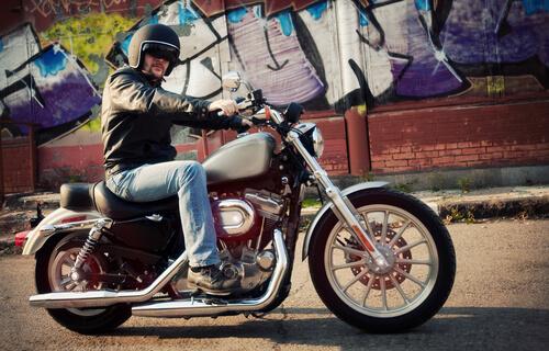 Man on motorcycle posing in front of Orange County street mural