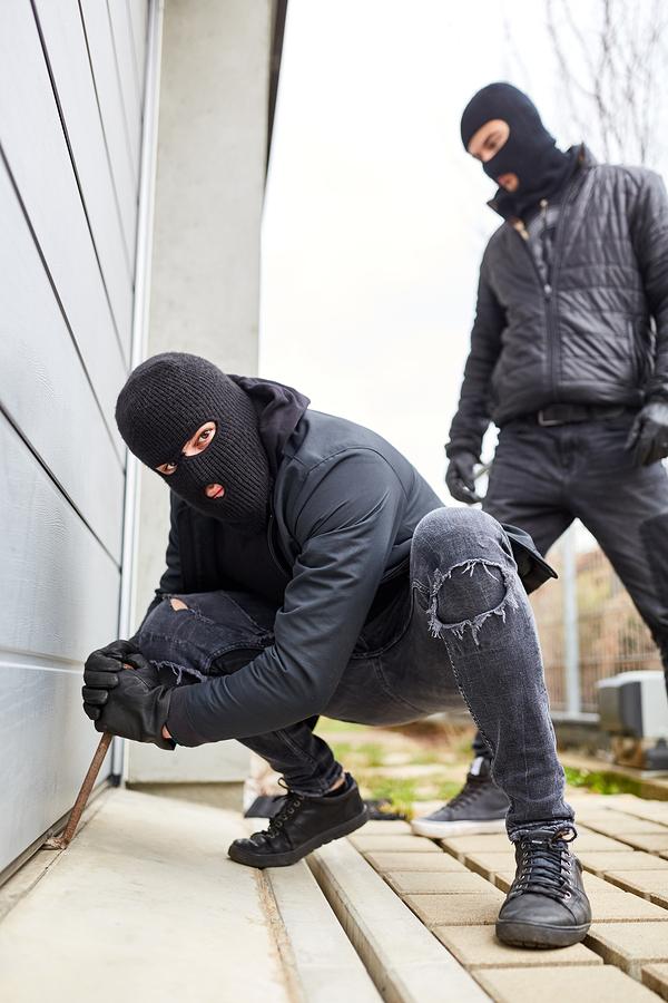 Bigstock two burglars at gate of garage 312331675