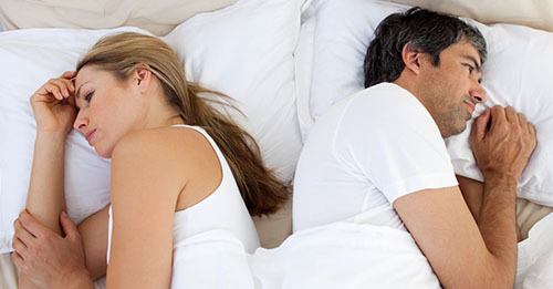 people in bed with back turned