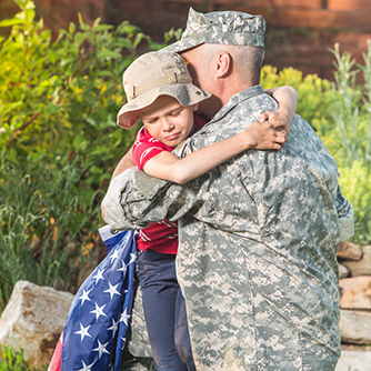 man in miltary uniform hugging child