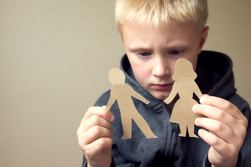 Child holding a ripped up paper couple