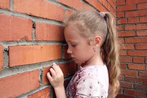 girl facing brick wall