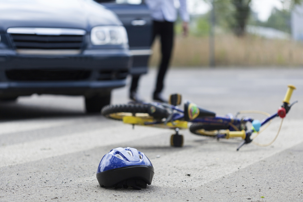 Childs bicycle and helmet laying on the ground after being hit by a car