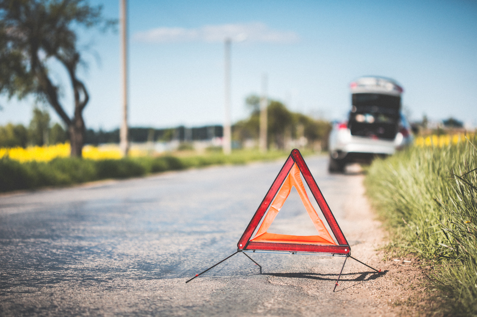 Red warning triangle and broken car at the side of the road picjumbo com