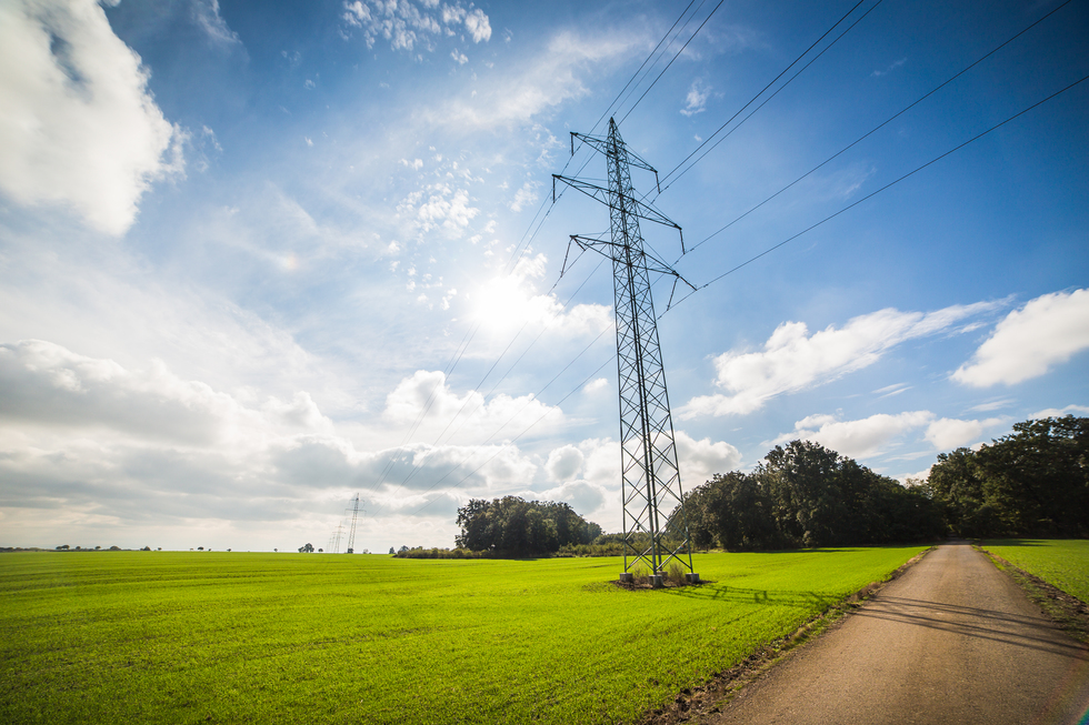 Road under power line electricity pylons picjumbo com