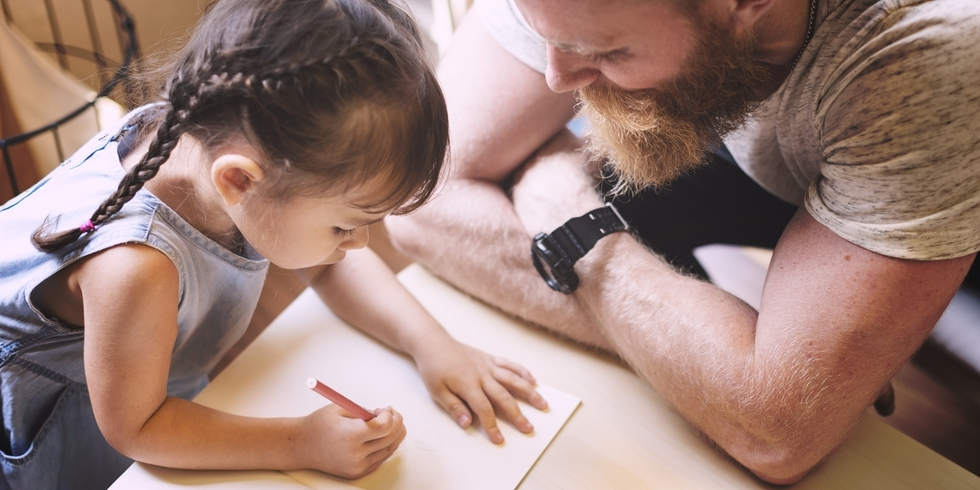Child Custody Dad watching young daughter drawing a picture