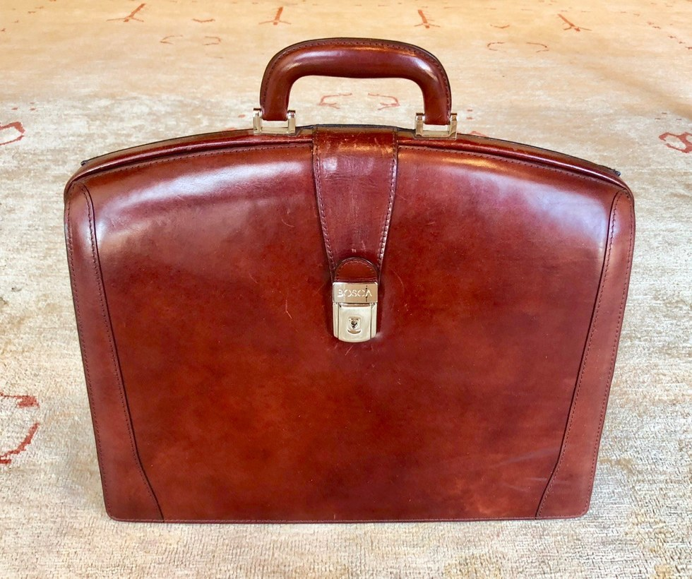 Brown leather Bosca briefcase of Attorney Peter J. Diiorio on rug at New Orleans Legal LLC