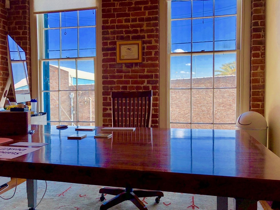 Office room with meeting table desk and chairs with blue skies in windows for New Orleans Legal LLC and Attorney Peter J. Diiorio