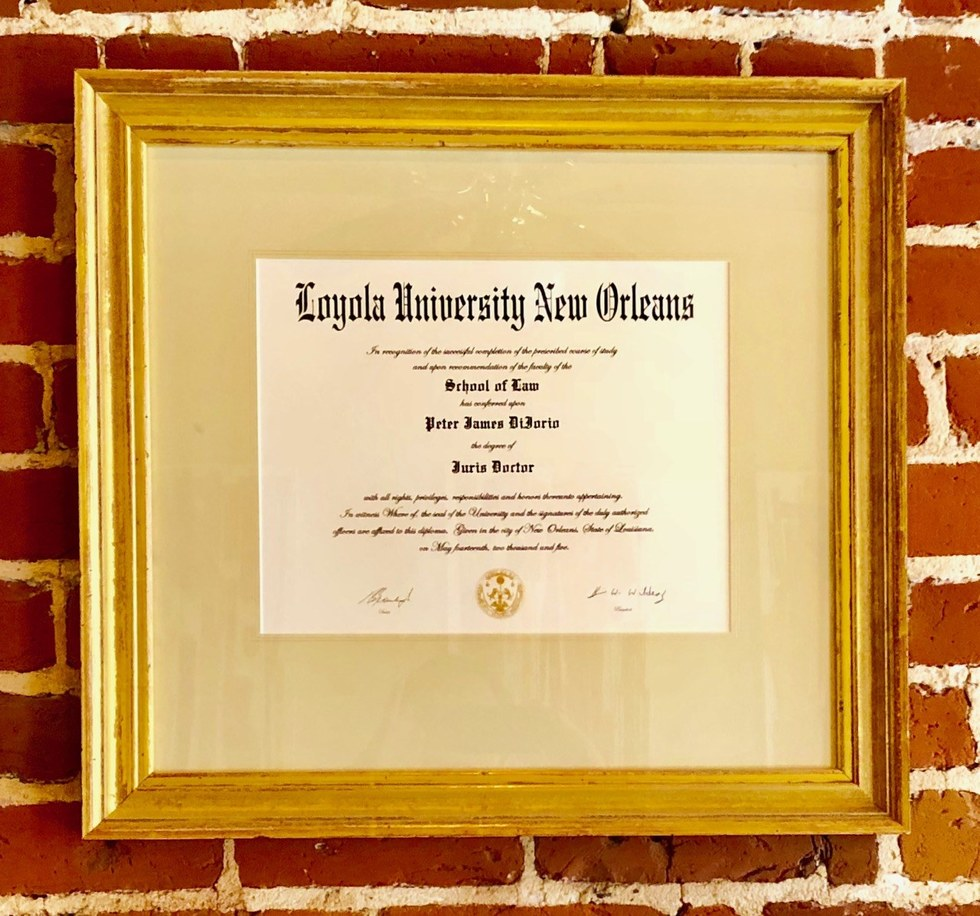 Framed Loyola law school diploma of Attorney Peter J. Diiorio on brick wall at New Orleans Legal, LLC