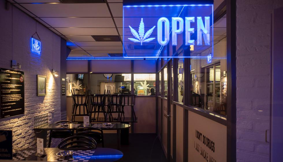 A retail cannabis shop with an illuminated open sign.