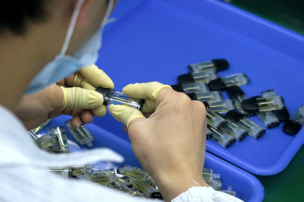 A worker assembles and checks cartridges for vape pens.
