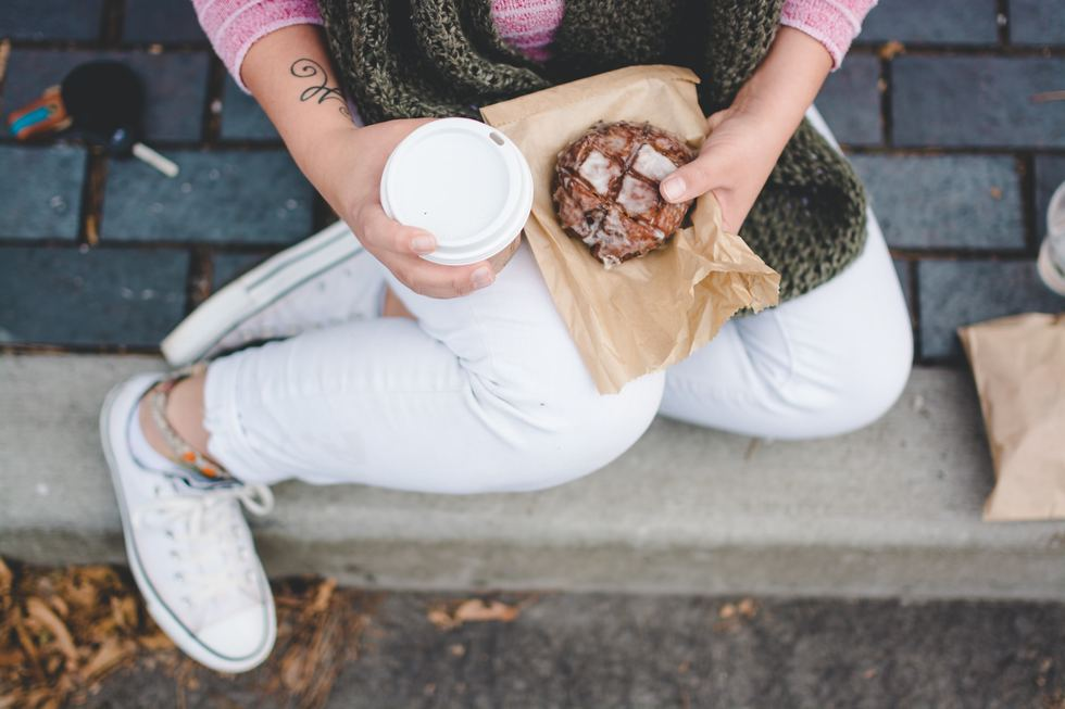 Woman holding coffee cup and muffin